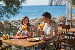 Молодые пары в кафе пляжа Стоковые Фотографии RF