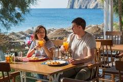 Молодые пары в кафе пляжа Стоковая Фотография RF