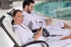молодые пары в купальных халатах используя цифровые приборы пока отдыхающ около бассейна стоковые изображения rf