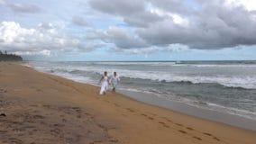 Молодые пары в любов бежать вдоль пустого пляжа океана на заходе солнца, держа руки сток-видео