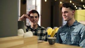 Молодые пары в обмундированиях стильного битника городских сидя в открытом со-работая космосе, обсуждая что-то пока указывающ акции видеоматериалы