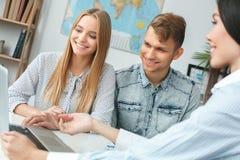 Молодые пары в связи агенства путешествия при агент по путешествиям путешествуя концепция представляя назначения стоковое фото