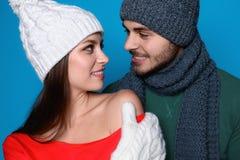 Молодые пары в теплых одеждах на предпосылке цвета Стоковая Фотография RF