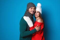 Молодые пары в теплых одеждах на предпосылке цвета Стоковые Фотографии RF