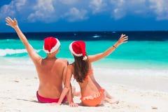 Молодые пары в шляпах santa имея потеху на тропическом пляже Новый Год, Стоковые Фото