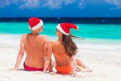 Молодые пары в шляпах santa имея потеху на тропическом пляже Новый Год, Стоковое Изображение