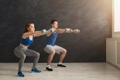 Молодые пары в sportswear делая сидение на корточках Стоковое Изображение RF