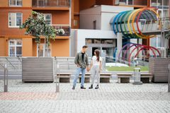 Молодые пары датировка в влюбленности идя в город Бизнесмены или коллеги офиса flirting после работы держа руки на улице Стоковая Фотография RF