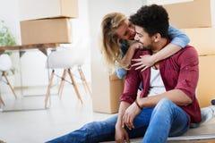 Молодые пары двигая в новый дом и распаковывая коробки carboard Стоковые Фотографии RF