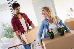 Молодые пары двигая в новый дом и распаковывая коробки carboard Стоковое фото RF