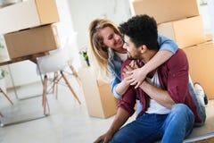 Молодые пары двигая в новый дом и распаковывая коробки carboard Стоковые Изображения