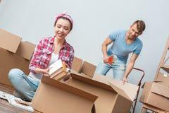 Молодые пары двигая к женщине нового места пакуя кладя книги в коробку dreamful пока запись на ленту человека счастливое стоковое изображение rf