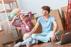 Молодые пары двигая к женщине нового места сидя играя со смеяться палитры счастливый с человеком стоковые фото