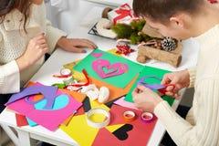 Молодые пары делая сердца от бумаги для дня валентинки, взгляд сверху - романтичного и концепции влюбленности стоковое изображение rf