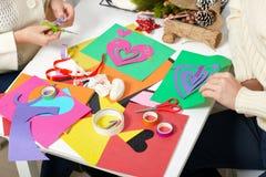 Молодые пары делая украшения от бумаги для дня валентинки, взгляд сверху - романтичного и концепции влюбленности стоковые фото