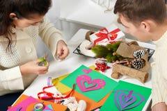 Молодые пары делая украшения от бумаги для дня валентинки, взгляд сверху - романтичного и концепции влюбленности стоковое изображение