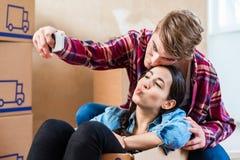 Молодые пары делая selfie для того чтобы делить утеху двигать внутри в Стоковая Фотография RF