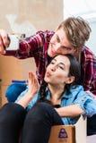 Молодые пары делая selfie для того чтобы делить утеху двигать внутри в Стоковое Изображение RF