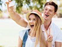 Молодые пары делая selfie outdoors Стоковое Изображение