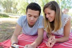 Молодые пары деля наушники на outdoors одеяла стоковые фото