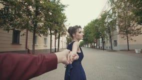 Молодые пары держа парня женщины рук ведущий идя в улицу