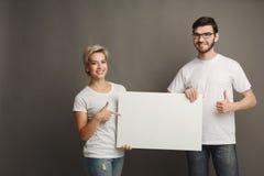 Молодые пары держа пустое белое знамя Стоковые Фото