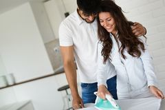 Молодые пары дома делая работы по дому и утюжить hosehold Стоковые Фото