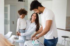 Молодые пары дома делая работы по дому и утюжить hosehold Стоковое Изображение