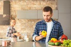 Молодые пары дома стоя в человеке кухни совместно держа варить жены промежутка времени болгарского перца внимательный радостный стоковые фото