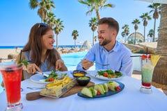Молодые пары есть в ресторане бассейна Стоковые Изображения RF