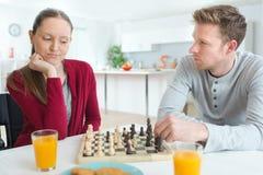 Молодые пары играя интерьер шахмат дома Стоковая Фотография