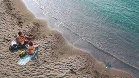 Молодые пары играя музыку и поя совместно на пляже видеоматериал