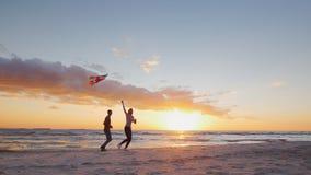 Молодые пары играя со змеем на пляже на заходе солнца Съемка замедленного движения Steradicam сток-видео