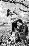 Молодые пары играя с собаками outdoors в осени стоковые фотографии rf