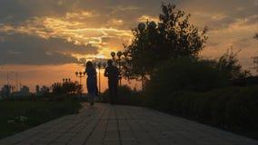 Молодые пары идя в заход солнца скольжение стоковые изображения