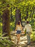 Молодые пары идя в лес стоковое изображение rf
