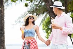 Молодые пары идя в парк на взморье держа руки счастливые туристы человека и женщины говоря на каникулах Стоковое Изображение RF