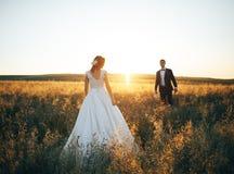 Молодые пары идя в пшеничное поле на заходе солнца стоковое фото rf