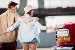 Молодые пары идя около автомобиля Стоковая Фотография RF