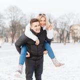 Молодые пары идя через город Парень носит девушку Стоковое Фото