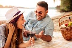 Молодые пары имея пикник на пляже Лежащ на одеяле пикника, выпивая вине и говорить стоковые изображения