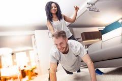 Молодые пары имея потеху делая гимнастику дома стоковое изображение