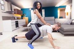 Молодые пары имея потеху делая гимнастику дома стоковая фотография