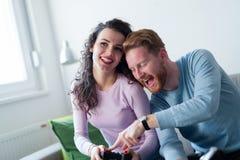 Молодые пары имея потеху играя видеоигры Стоковое Изображение RF