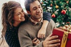 Молодые пары имея потеху празднуя рождество с подарками Стоковое фото RF