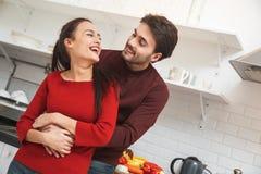 Молодые пары имея романтичный выравниваться дома в кухне смеясь над смотрящ один другого Стоковые Изображения