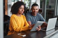 Молодые пары используя цифровой планшет в кафе стоковые фото