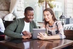 Молодые пары используя цифровую таблетку в кафе Стоковые Изображения RF