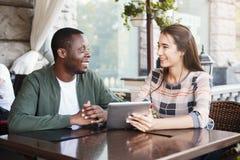 Молодые пары используя цифровую таблетку в кафе Стоковое Изображение