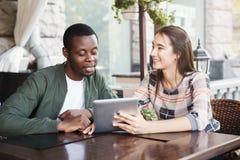 Молодые пары используя цифровую таблетку в кафе стоковые фото